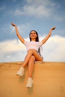 Una donna sorridente si siede su un molo e alza le mani