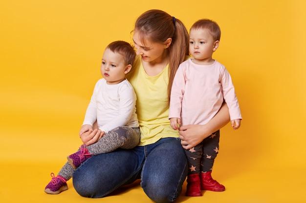 La donna sorridente si siede con le sue figlie bionde, abbraccia i bambini e si sente felice.