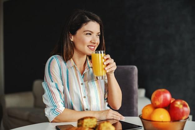 Donna sorridente seduta al tavolo da pranzo al mattino e facendo una sana colazione
