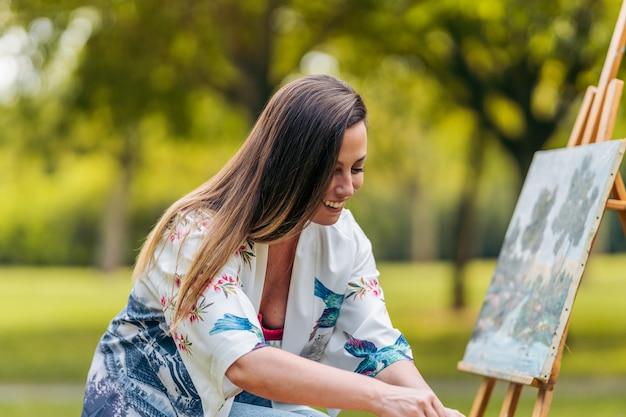 Donna sorridente seduta in un parco davanti a una tela che fa male