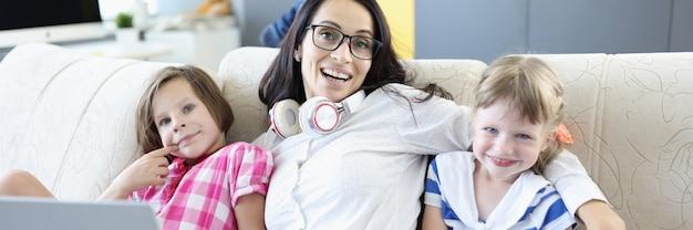 Donna sorridente che si siede con il computer portatile e i bambini sul divano.