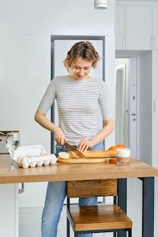 Donna sorridente affettare baguette sul tagliere di legno in cucina