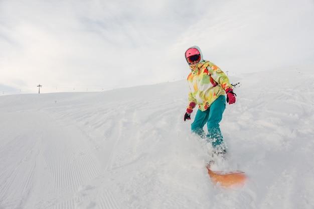 Snowboarder sorridente della donna in abiti sportivi luminosi che guidano giù il pendio di montagna contro il cielo