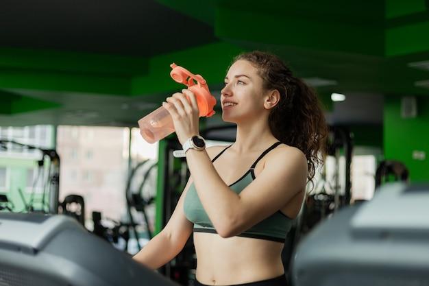 Donna sorridente in abbigliamento sportivo corre su un tapis roulant e beve acqua in palestra. il concetto di uno stile di vita sano, riscaldamento, fitness, perdita di peso.