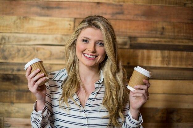 Donna sorridente che sta con la tazza di caffè eliminabile in caffè