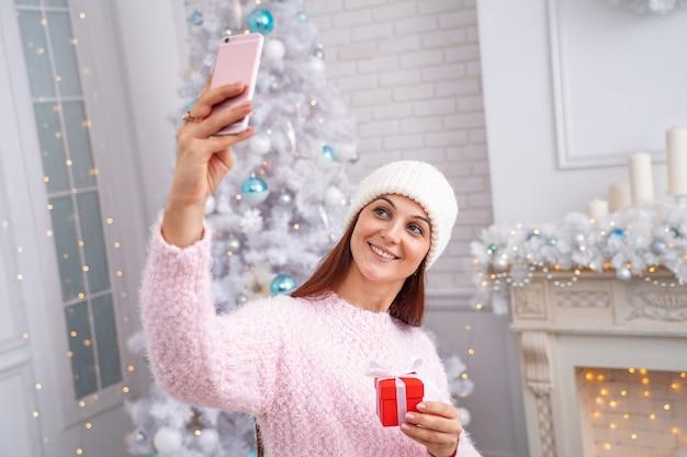 Donna sorridente in un maglione e cappello prendendo un selfie su uno smartphone