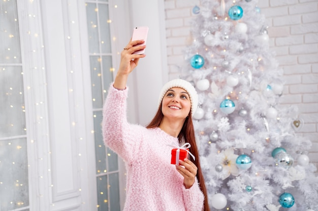 Donna sorridente in un maglione e cappello prendendo un selfie