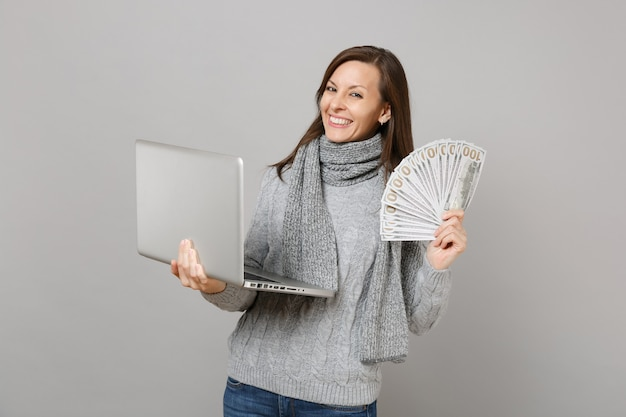 La donna sorridente in maglione che lavora al computer del pc portatile tiene un sacco di dollari banconote denaro contante isolato su sfondo grigio. stile di vita sano, consulenza sul trattamento online, concetto di stagione fredda.