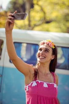Donna sorridente che prende un selfie in parco