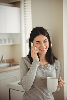 Donna sorridente che parla sul telefono cellulare mentre si tiene la tazza di caffè
