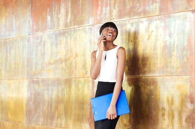 Donna sorridente che parla al telefono in ufficio