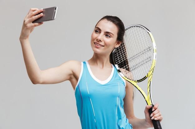 Giocatore di tennis della donna sorridente che tiene la racchetta isolata sopra il muro grigio, prendendo selfie