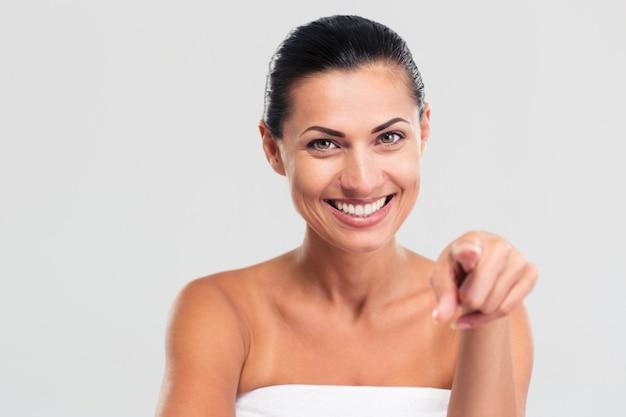 Donna sorridente in asciugamano puntare il dito alla telecamera