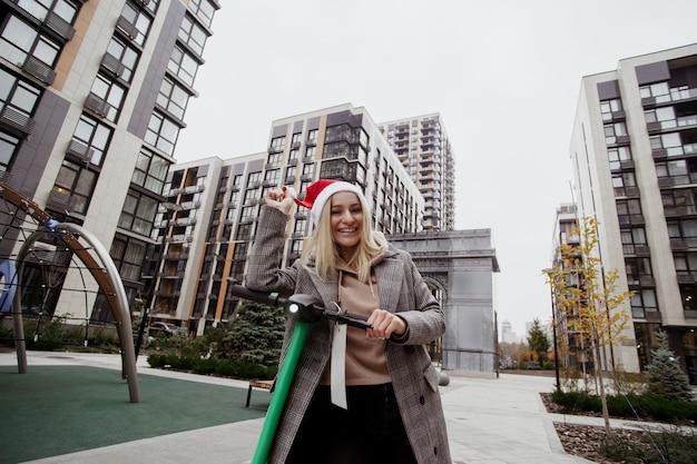 La donna sorridente viaggia su uno scooter elettrico in affitto per la città. lei gioca con il suo cappello rosso da babbo natale e ride. giovane donna bionda allegra in cappotto casual buon trascorrere del tempo.