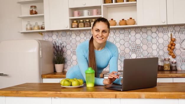 Donna sorridente che utilizza computer nell'interno moderno della cucina. cucina e concetto di stile di vita sano. una donna guarda la telecamera e sorride