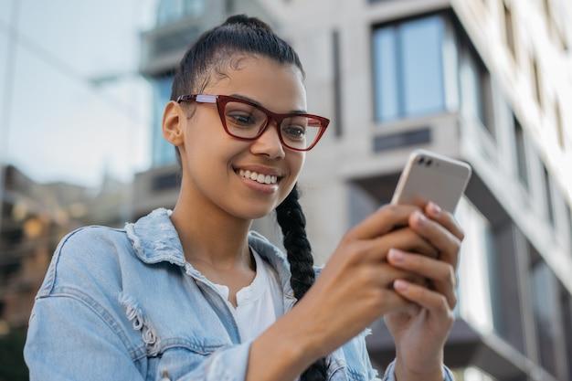 Donna sorridente utilizzando i messaggi di testo di comunicazione del telefono cellulare con videochiamata