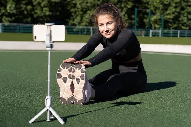 Donna sorridente vlogger in abiti sportivi che si siede sul tappeto erboso artificiale all'aperto Foto Premium
