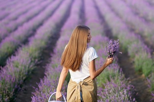 Donna sorridente che cammina con il campo di lavanda del cesto
