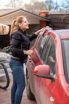 Donna sorridente che lava il tetto dell'auto con uno straccio