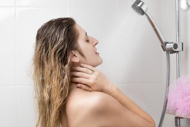 Donna sorridente che si lava sotto la doccia