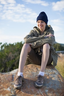 Cappuccio da portare sorridente della donna che si siede su una roccia