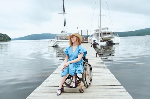 Donna sorridente in sedia a rotelle in piedi sul molo di legno godendo le vacanze estive in mare.