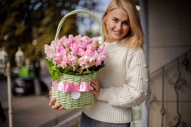 Donna sorridente in maglione bianco carino tenendo un bel cesto di vimini verde con fiori rosa