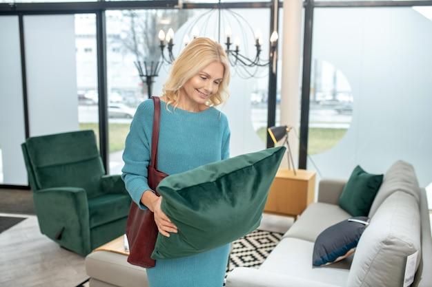 Donna sorridente con una borsa sulla spalla in piedi nel negozio di mobili con un piccolo cuscino verde tra le mani, che sembra gioiosa.
