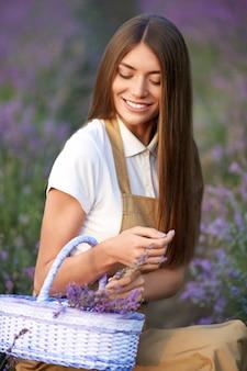 Donna sorridente con cesto di campo di lavanda