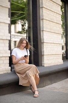 Donna sorridente con i capelli biondi in una t-shirt bianca che utilizza smartphone mentre è seduta per strada sullo sfondo di una grande finestra vicino a un edificio in mattoni