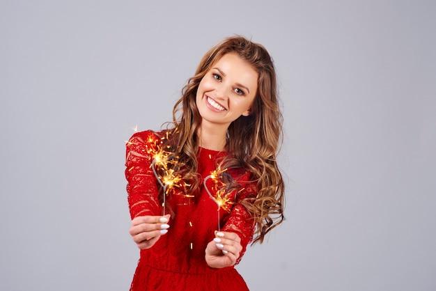 Donna sorridente con stelle filanti accese