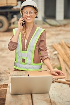 Donna sorridente con un gadget appoggiato una mano sul tavolo