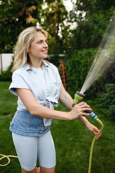 Donna sorridente con tubo flessibile irrigazione alberi in giardino