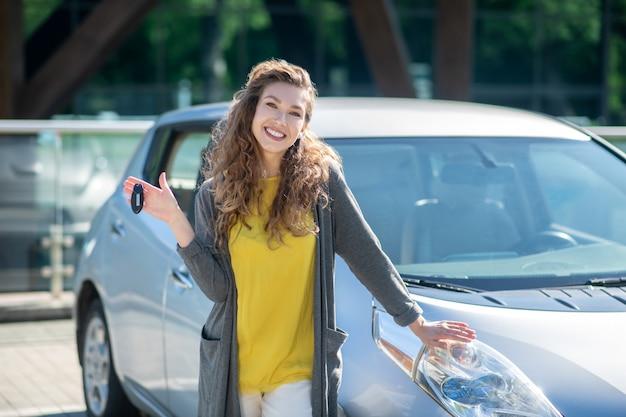 Donna sorridente con le chiavi che stanno vicino all'automobile grigia