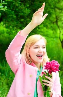 Donna sorridente con fiore di peonia agitando la mano