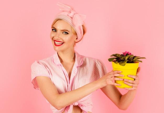 Donna sorridente con fiore in vaso saintpaulia. ragazza che coltiva fiori. violette africane di saintpaulia.