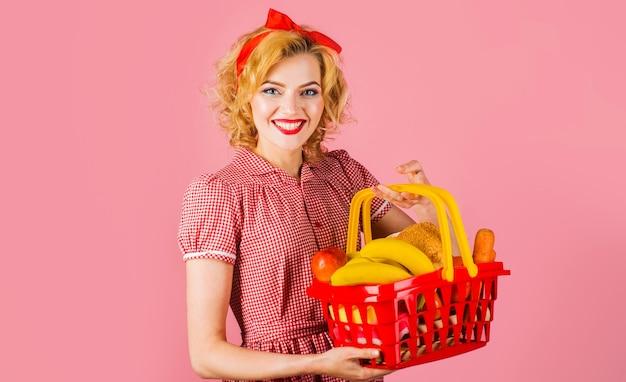 Donna sorridente con cestino della spesa con generi alimentari in supermercato. acquisti folli.