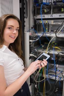 Donna sorridente con tablet pc controllando i server