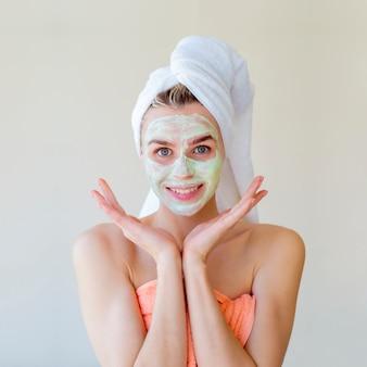 La donna sorridente con un asciugamano si mette una crema sul viso, le piace.