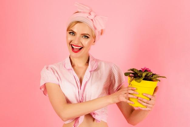 Donna sorridente con fiore viola in vaso, ragazza che coltiva fiori, pianta.