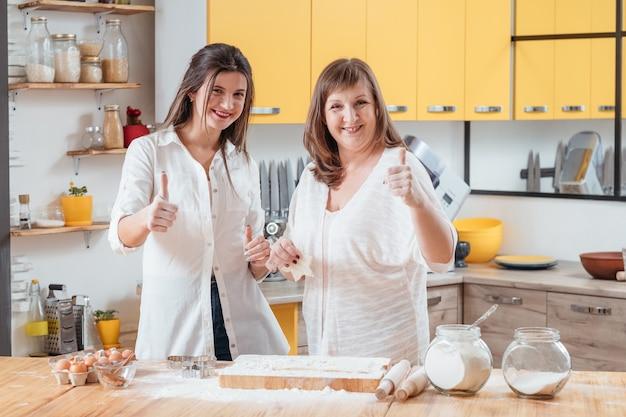 Donne sorridenti che posano nella cucina della famiglia