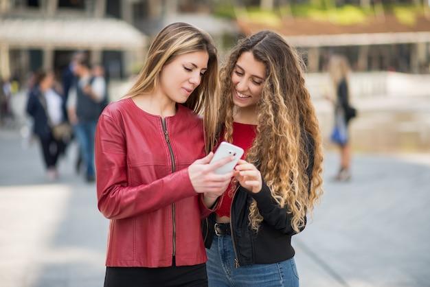Donne sorridenti che utilizzano un telefono cellulare all'aperto in una città