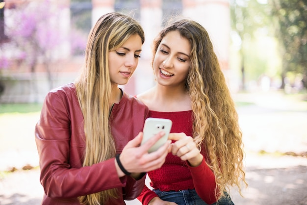 Donne sorridenti che utilizzano un telefono cellulare all'aperto