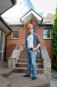 Operaio sorridente in posa davanti a casa con scala in pietra
