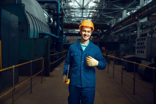 Il lavoratore sorridente in uniforme e casco di sicurezza tiene il taccuino
