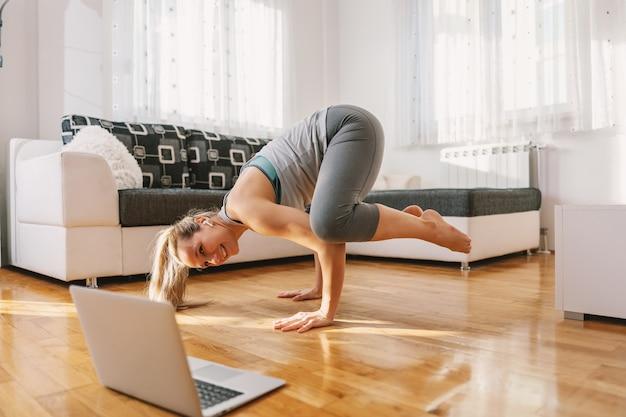 Istruttore sorridente di yoga nella posa di yoga del corvo che ha lezione in linea sopra il computer portatile