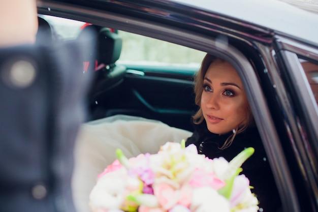 Giovane mazzo adulto sorridente della tenuta della sposa dei fiori che guardano dalla finestra delle limousine il giorno nevoso e invernale.
