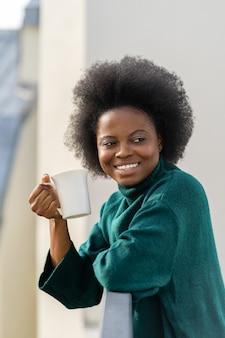 Giovane donna biracial afroamericana sorridente che gode di una tazza di tè o di caffè