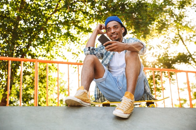 Sorridente giovane uomo africano in auricolari