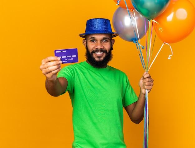 Sorridente giovane ragazzo afro-americano che indossa un cappello da festa con palloncini e porgendo la carta di credito alla telecamera